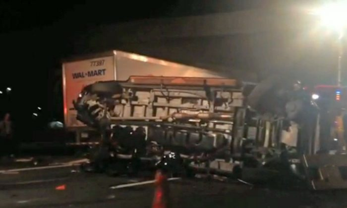 In this image from video the limousine bus carrying Tracy Morgan and six other people lies on its side early Saturday morning June 7, 2014 on the New Jersey Turnpike. (AP Photo/Will Vaultz Photography)