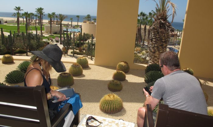 Couple on holiday in Cabo, Mexico, immersed in their smart technology devices. (Lina Broydo)