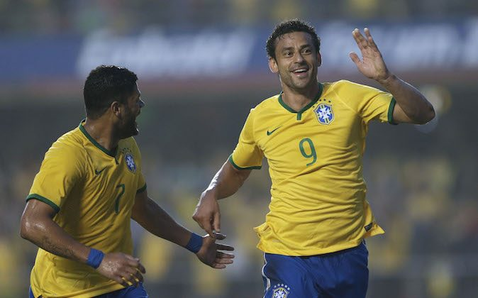 Brazil's Fred, right, celebrates with teammate Hulk after scoring against Serbia during a friendly soccer match at Morumbi stadium in Sao Paulo, Brazil, Friday, June 6, 2014. Brazil is hosting the World Cup soccer tournament that starts June 12. (AP Photo/Andre Penner)