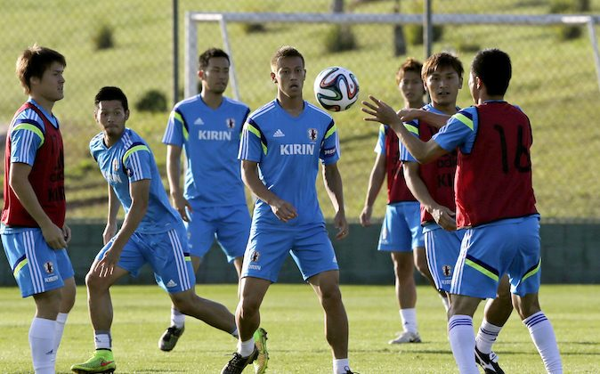 Japan's Keisuke Honda, center, watches a teammate throwing a ball during a training session of Japan in Itu  Brazil, Wednesday, June 11, 2014.  Japan play in group C of the 2014 soccer World Cup. (AP Photo/Shuji Kajiyama)