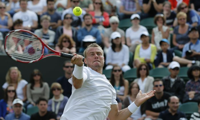 Lleyton Hewitt of Australia plays a return to Jerzy Janowicz of Poland during a men's singles match at the All England Lawn Tennis Championships in Wimbledon, London, Friday, June 27, 2014. (AP Photo/Ben Curtis)