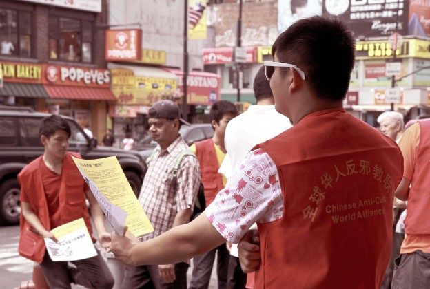 A group of 16-year-old youths try to distribute Chinese Communist Party propaganda in Flushing, New York, on Aug. 10, 2013. (Milene Fernandez/Epoch Times)