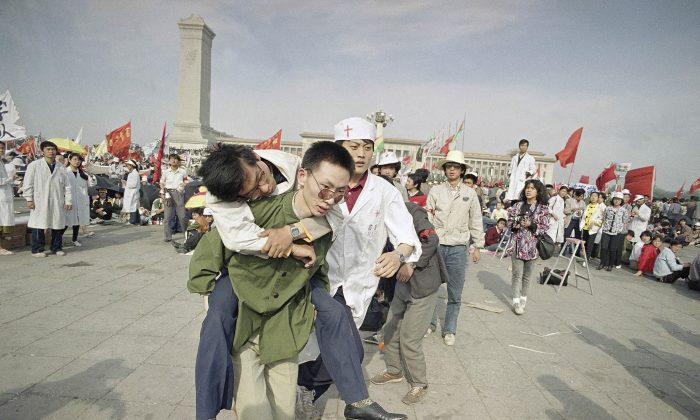 Medics rush a Beijing University student from Tiananmen Square after he collapsed on the third day of a hunger strike on May 16, 1989. A quarter century after the Communist Party's attack on demonstrations centered on Tiananmen Square on June 4, 1989, the ruling party prohibits public discussion and 1989 is banned from textbooks and Chinese websites. (AP Photo/Sadayuki Mikami)