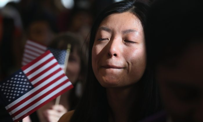 Chinese immigrant and hedge fund worker Yi Shu holds back tears after taking the oath of citizenship at a naturalization ceremony in New York on April 9, 2013. (John Moore/Getty Images)