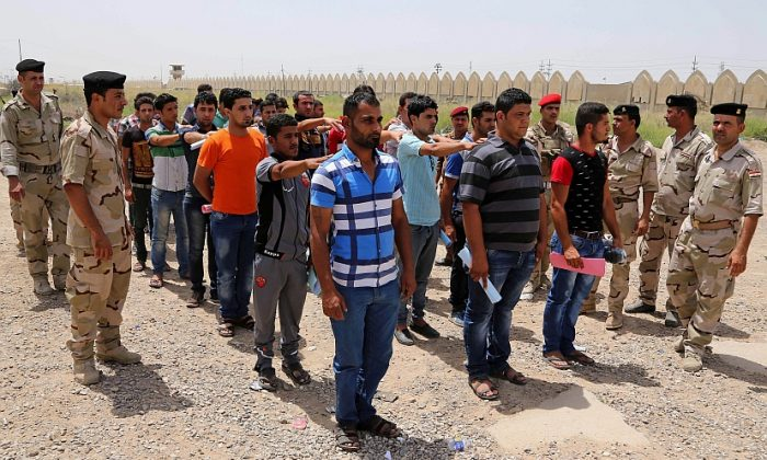 Iraqi men lining up outside of the main army recruiting center to volunteer for military service in Baghdad, Iraq, June 12.(AP Photo/ Karim Kadim, File)