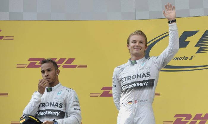 (L-R) Second placed Mercedes' British driver Lewis Hamilton, and teammate winner Mercedes' German driver Nico Rosberg wave on the podium after the Austrian Formula One Grand Prix at the Red Bull Ring in Spielberg on June 22, 2014. (Christof Stache/AFP/Getty Images)
