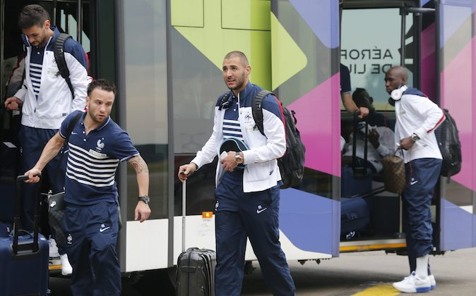 Members of France's soccer team, left from right, Hugo Lloris, Mathieu Valbuena, Karim Benzema and Rio Mavuda arrive at Lille -Lesquin  Airport as they prepare to travel to Brazil for the World Cup soccer tournament, in Lesquin northern France, Monday, June 9, 2014. France is part of Group E  that includes  Ecuador, Switzerland and Honduras. will play  Honduras in Porto Alegre in its opening match on June 15. (AP Photo/Jacques Brinon)