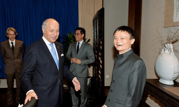 French Foreign Minister Laurent Fabius (L) meets with Jack Ma (R), chairman and founder of the Chinese e-commerce company Alibaba on May 16. A U.S. government report warns potential investors of the risks of investing in U.S.-listed Chinese companies, like Alibaba. (MARK RALSTON/AFP/Getty)