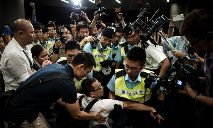 Riot police remove protesters from the grounds of the Legislative Council in Hong Kong, June 14, 2014. The protesters object to the government's plan to turn farmlands into housing estates. (Philippe Lopez/AFP/Getty Images)