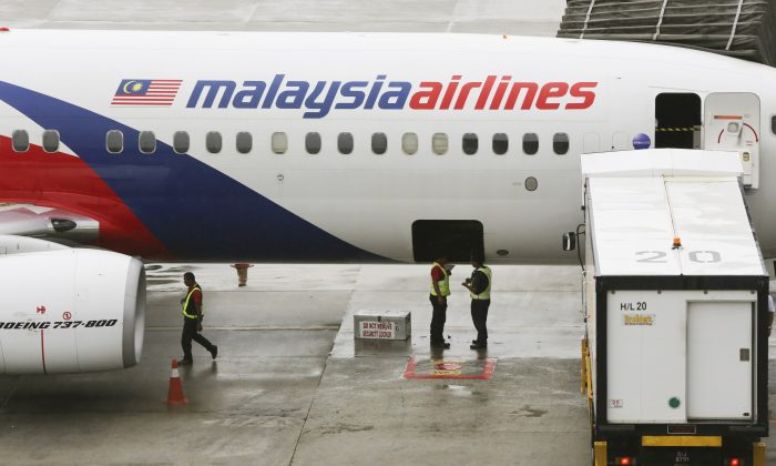 Ground crew stand near a Malaysia Airlines aircraft on the tarmac at the Kuala Lumpur International Airport (KLIA) in Sepang, Malaysia, Tuesday, May 27, 2014. (AP Photo/Vincent Thian)