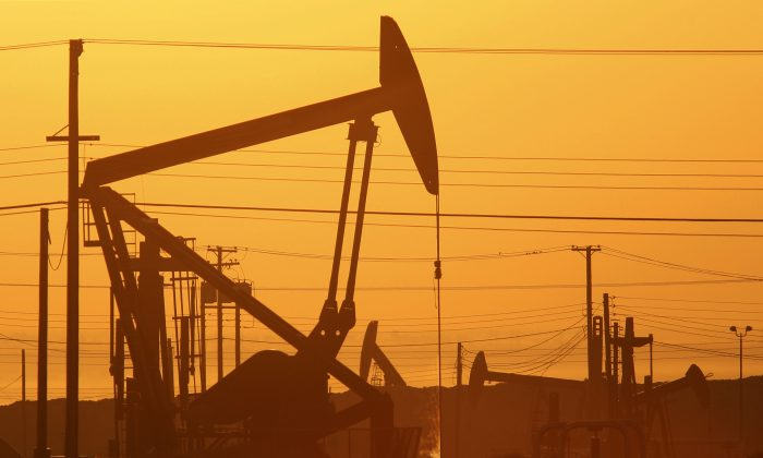 Pump jacks are seen at dawn in an oil field on March 24, 2014, near Lost Hills, Calif. Cheaper energy has made manufacturing in the United States more competitive, helping poise the U.S. economy for growth. (David McNew/Getty Images)