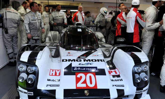 Mark Webber and his crew look at the expired #20 Porsche 919 Hybrid  in the paddock during the 82nd edition of the Le Mans 24-hours, on June 15, 2014 in Le Mans, western France. (Guillaume Souvant/AFP/Getty Images)