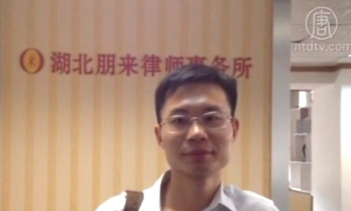 """Zhang Keke, a Wuhan lawyer, protested the suspension of his """"annual assessment"""" in front of the Wuhan Bar Association office by going on hunger strike. June 12, 2014. (Courtesy of NTD Television)"""