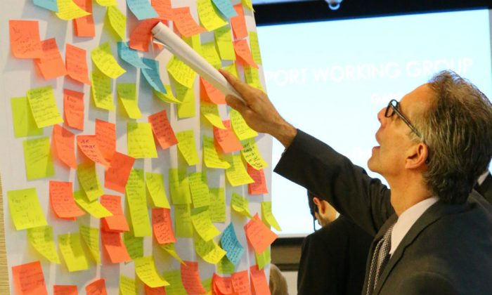 A man examines feedback on post-it notes from the community at the Seaport Working Group public presentation in New York on June 2, 2014. (Brendon Fallon/Epoch Times)