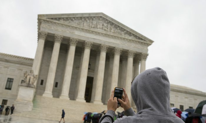A visitor to the Supreme Court uses his cellphone to take a photo, April 29. (AP Photo)
