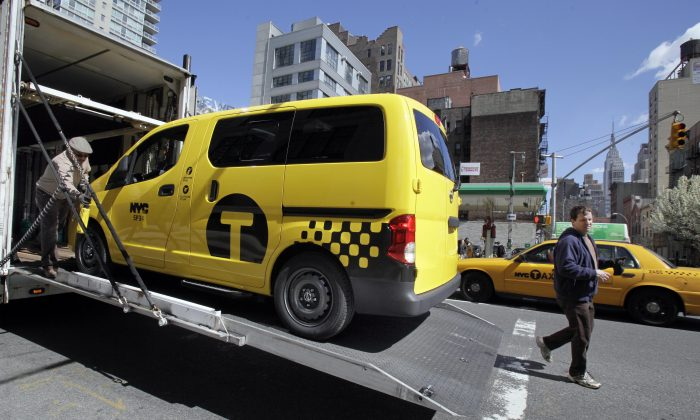 A prototype of the Nissan NV 200 New York City taxi is off-loaded from a truck, in New York, Monday, April 2, 2012. (AP Photo/Richard Drew)