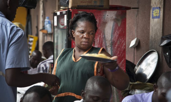 34-year-old single mother Madinah Nalukenge serves dishes to customers at her food stall, frequented by transport operators, on the edge of a bus terminal in the capital Kampala, Uganda, May 30, 2014. (AP Photo/Rebecca Vassie)