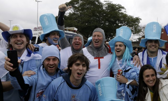Fans of England and Uruguay cheer for their national teams outside the Itaquerao Stadium before the group D World Cup soccer match between Uruguay and England in Sao Paulo, Brazil, Thursday, June 19, 2014. (AP Photo/Thanassis Stavrakis)