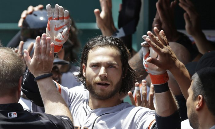 San Francisco Giants' Brandon Crawford is congratulated in the dugout after hitting a three-run home run off Cincinnati Reds starting pitcher Mike Leake in the fourth inning of a baseball game, Thursday, June 5, 2014, in Cincinnati. (AP Photo/Al Behrman)