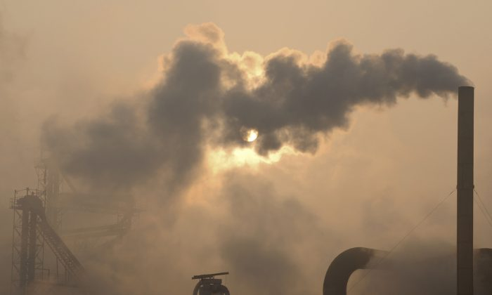 Smoke is emitted from chimneys of a cement plant in Binzhou City, Shandong Province, China, on Jan. 17, 2013. (AP Photo)