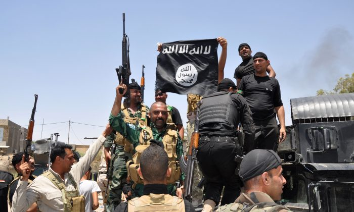 In this Saturday, June 28, 2014 photo, Iraqi security forces hold up a flag of the Islamic State in Iraq and the Levant t. (AP Photo)