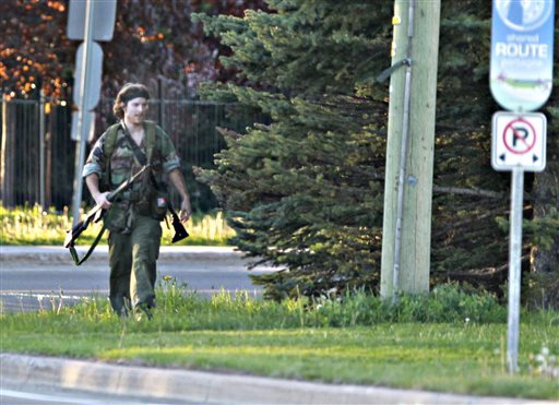 A heavily armed man that police have identified as Justin Bourque walks on Hildegard Drive in Moncton, New Brunswick, on Wednesday, June 4, 2014, after several shots were fired in the area. The man, suspected of killing three Royal Canadian Mounted Police officers, was spotted three times Thursday but has so far eluded a massive manhunt, police said. (AP Photo/The Canadian Press, Moncton Times & Transcript, telegraphjournal.com, Viktor Pivovarov)