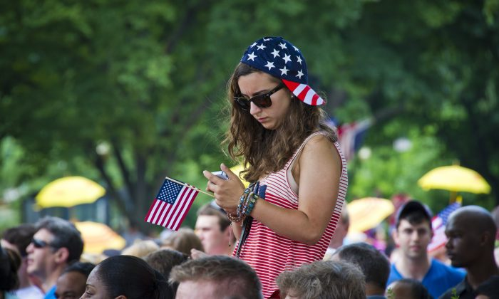 A girl checks her cellphone during the annual Independence Day Parade in Washington, D.C., July 04, 2013. (Mladen Antonov/AFP/Getty Images)