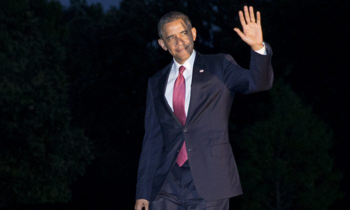 President Barack Obama waves to the media as he returns at dusk on the South Lawn of the White House in Washington, Friday, June 6, 2014, after attending remembrance activities on the 70th anniversary of D-Day in Normandy, France. (AP Photo/Jacquelyn Martin)