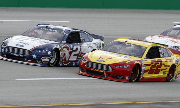 Brad Keselowski (2) and Joey Logano (22) vie for the lead in the NASCAR Sprint Cup series auto race Saturday, June  28, 2014, at Kentucky Speedway in Sparta, Ky. (AP Photo/James Crisp)