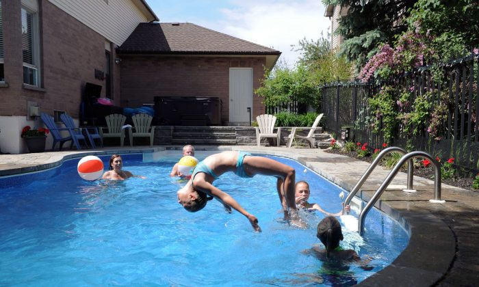 A family has fun in their backyard pool in Burlington, Ont. Drowning remains a leading cause of death for teens and children in Canada, and the BC Coroners Service says more effective water safety education is needed, especially for males aged between 15 and 18. (The Canadian Press/Galit Rodan)