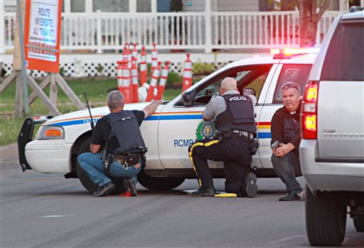 Police officers take cover behind their vehicles in Moncton, New Brunswick, on Wednesday June 4, 2014. Three police officers were shot dead and two others injured Wednesday in the east coast Canadian province of New Brunswick, officials said, and authorities were searching for a suspect. (AP Photo/Moncton Times & Transcript, Ron Ward via The Canadian Press)