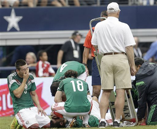 Mexico players gather around Luis Montes after he was injured in the first half of a friendly soccer match against Ecuador in Arlington, Texas, Saturday, May 31, 2014. (AP Photo/The Dallas Morning News, Brad Loper)