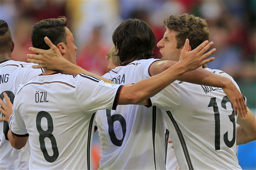 Germany's Thomas Mueller, right, celebrates with Mesut Ozil after scoring the opening goal during the group G World Cup soccer match between Germany and Portugal at the Arena Fonte Nova in Salvador, Brazil, Monday, June 16, 2014.  (AP Photo/Bernat Armangue)