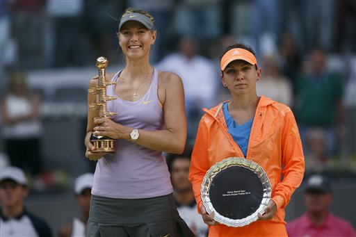 Maria Sharapova from Russia, left, celebrates her victory holding her trophy next to Simona Halep from Romania, right, during a Madrid Open tennis tournament final match in Madrid, Spain, Sunday, May 11, 2014. The pair meet in another final at the French Open on June 7.(AP Photo/Andres Kudacki)