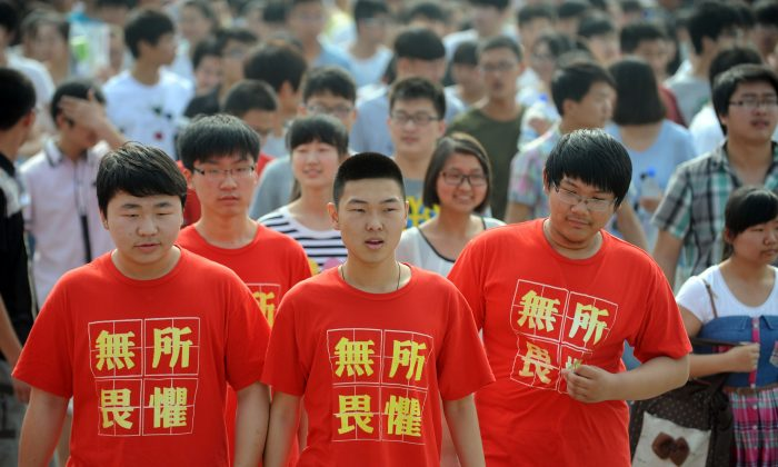 Students (front) wearing t-shirts saying 'fear nothing' walk into the exam room to sit the 2014 college entrance exam in Bozhou, east China's Anhui province on June 7, 2014. 9.4 million students took the exam this year, while another one million declined to. (AFP/Getty Images)