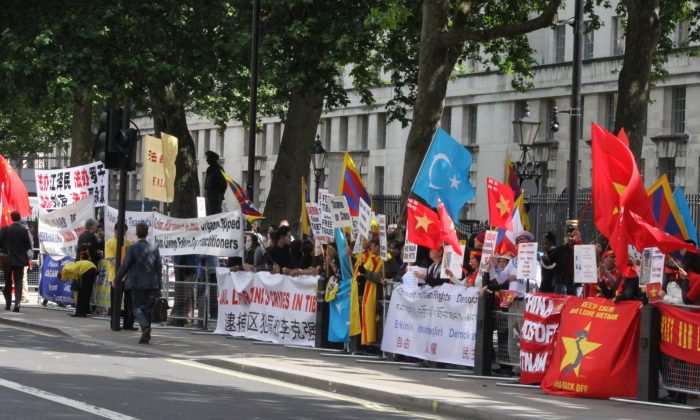 The Chinese Communist Party flag; Falun Gong banners; the red, blue and yellow flag of Tibet; the pale blue  flag of Uighuristan (Islamic Republic of East Turkestan); and the red Vietnamese flag with Flag of St George in the top corner to represent English Vietnamese; at Whitehall on June 17. (Wenjing/Da Ji Yuan)