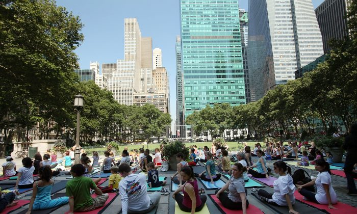 People participate in a free outdoor yoga class in Bryant Park on June 30, 2009, in New York City. After weeks of unseasonably wet weather, New York and New England have been experiencing dry and warm days, which have brought about a flurry of activity in area parks and recreation areas. (Photo by Spencer Platt/Getty Images)