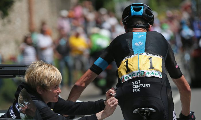 Chris Froome of Team Sky receives medical attention after being involved in a crash early in the race during Stage Four of the Tour de France. Froome crashed twice in Stage Five and was forced to abandon. (Doug Pensinger/Getty Images)