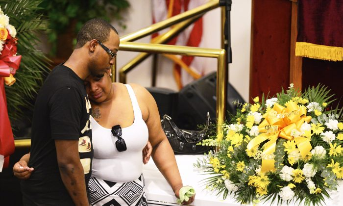 Emerald Garner (R) stands next to the coffin of her father, Eric Garner, during his funeral at Bethel Baptist Church in the Brooklyn borough of New York on July 23. (AP Photo/New York Daily News, James Keivom)
