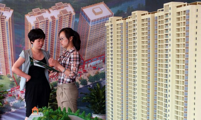 A Chinese homebuyer makes inquiries about a new apartment project on display at a real estate fair in Yichang, in central China's Hubei Province on May 18, 2012. (AFP/AFP/Getty Images)
