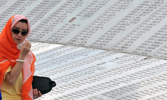 A Bosnian Muslim woman, survivor of the Srebrenica 1995 massacre, searches for names of her relatives among names of victims, engraved on a Memorial Wall at Srebrenica Memorial cemetery in Potocarion near Srebrenica, on July 10, 2014. (Elvis Barukcic/AFP/Getty Images)