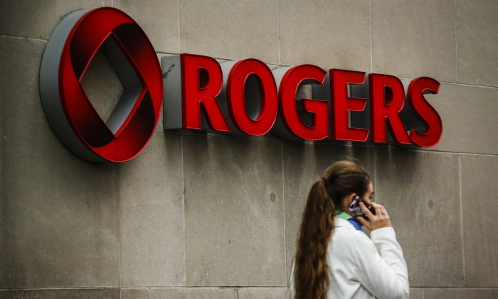 A woman speaks on her cell phone in front of a Rogers Communications Inc sign before the company's annual general meeting for shareholders in Toronto April 22, 2014. A recent Supreme Court decision has pushed Rogers and Telus to cease handing over customer information without a warrant when requested by police and government. (REUTERS/Mark Blinch)