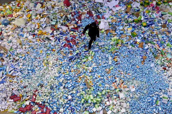 This picture taken on March 14 shows a Chinese policeman walking across a pile of fake medicines seized in Beijing in recent months. The rapid growth of Internet commerce has led to an explosion of counterfeit drugs sold around the world, with China the biggest source of fake medicines, pharmaceutical experts said as the illicit trade is now believed to be worth around 75 billion USD globally, with criminal gangs increasingly using the web to move their products across borders. (STR/AFP/Getty Images)