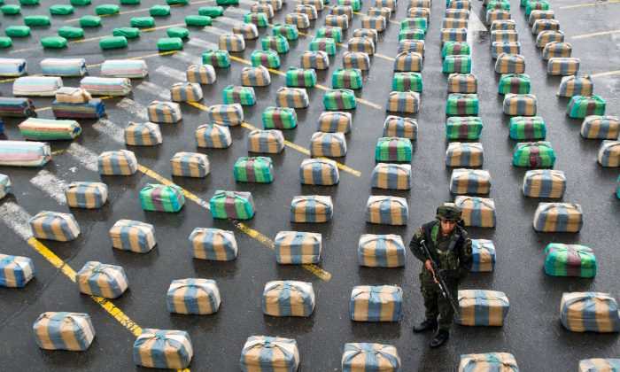 A Colombian member of a police anti-drugs unit stands guard next to marijuana packages displayed to the press, on March 26, 2013, in Cali, department of Valle del Cauca, Colombia. Police seized 7.7 tons of marijuana during the operation 'Republica 39', carried out between the municipalities of Tulua and Buga, who belonged to the Revolutionary Armed Forces of Colombia (FARC) guerrillas. The Director General of the National Police of Colombia, General Jose Roberto Leon Riano, said that 80 tons of marijuana and 36 tons of cocaine have been seized so far this year. (Luis Robayo/AFP/Getty Images)