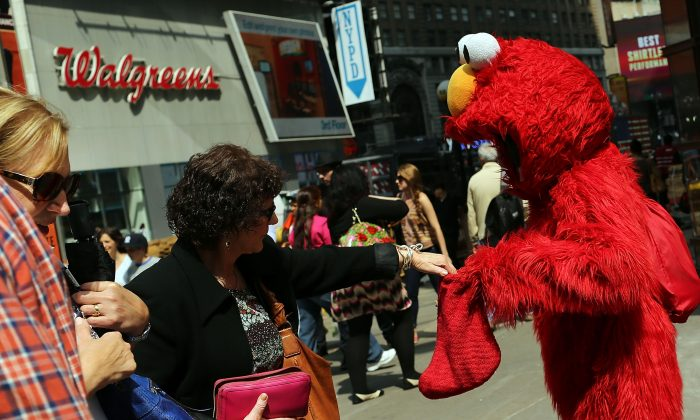 A tip is given to a man dressed as the Elmo children's television character after he posed for photos in Times Square, New York City, April 10, 2013. (Spencer Platt/Getty Images)
