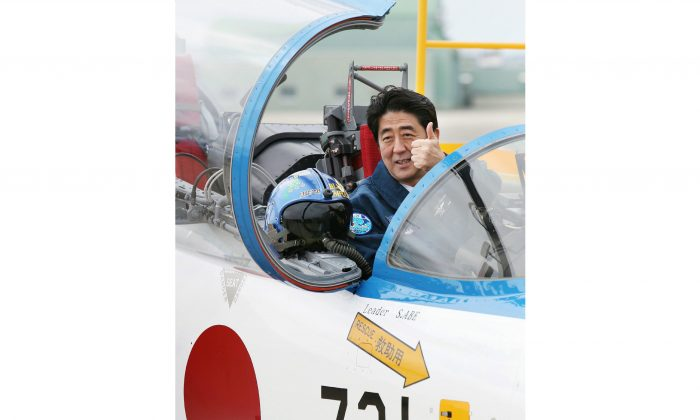 Japanese Prime Minister Shinzo Abe poses inside a T-4 training jet plane of the Air Self-Defense Force's Blue Impulse flight team at the ASDF base in Higashimatsushima, Miyagi Prefecture, on May 12, 2013. Abe has recently announced a policy committing Japan to defending its allies, an expansion of the permitted use of Japan's military forces. (Jiji Press/AFP/Getty Images)