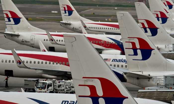 Airport groundstaff walk past Malaysia Airlines planes parked on the tarmac at the Kuala Lumpur International Airport in Sepang on June 17, 2014. (Manan Vatsyanyana/AFP/Getty Images)