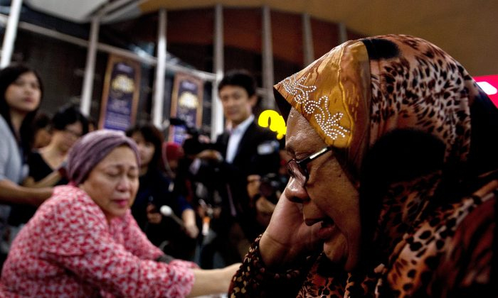"""Relatives of people onboard Malaysia Airlines flight MH17 from Amsterdam react outside the family holding area at the Kuala Lumpur International Airport in Sepang on July 18, 2014. A Malaysian airliner carrying 295 people from Amsterdam to Kuala Lumpur crashed on July 17 in rebel-held east Ukraine, as Kiev said the jet was shot down in a """"terrorist"""" attack. Ukraine's government and pro-Russian insurgents traded blame for the disaster, with comments attributed to a rebel commander suggesting his men may have downed Malaysia Airlines flight MH17 by mistake, believing it was a Ukrainian army transport plane. (MANAN VATSYAYANA/AFP/Getty Images)"""
