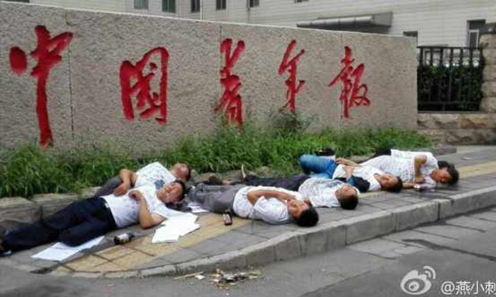 Seven petitioners lay on the ground, seemingly unconscious, several appearing to foam at the mouth, after drinking pesticide in a group suicide attempt outside the offices of the China Youth Daily in Beijing on July 16. They staged the attempted suicide in protest of their houses being demolished with little compensation. (Weibo.com)