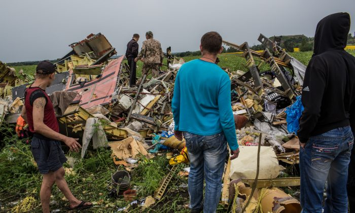 Men look at the wreckage of passenger plane Air Malaysia flight MH17 on July 18, 2014 in Grabovka, Ukraine. (Brendan Hoffman/Getty Images)